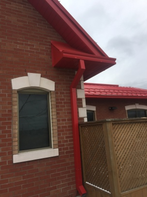 Red metal gutters and downspouts